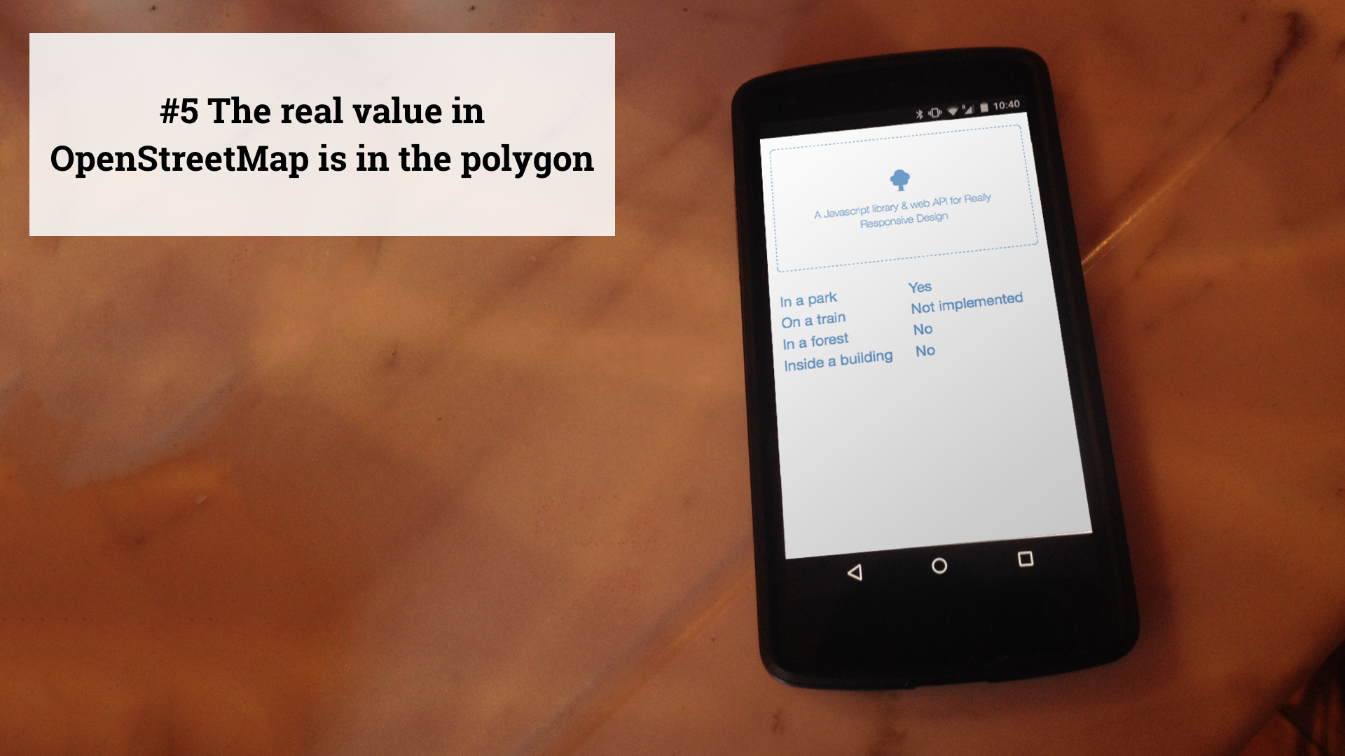 Slide 6 - The real value in OpenStreetMap is in the polygon - photo of a phone showing a test web page